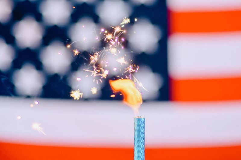 Close-Up Of Lit Candle With Sparks Against American Flag