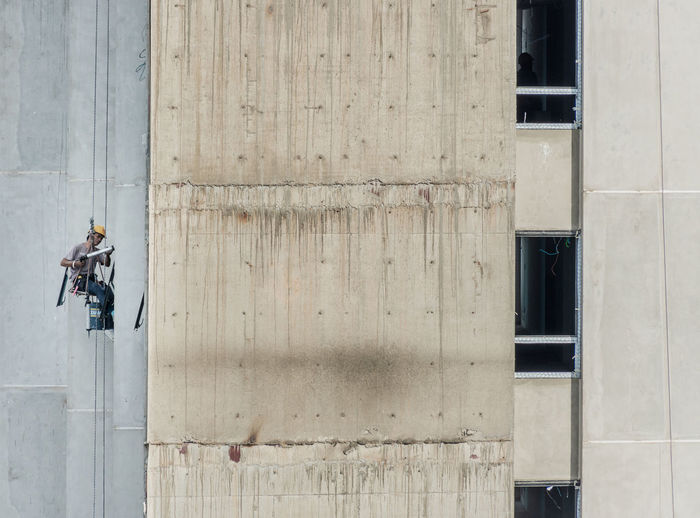 Construction worker hanging on building