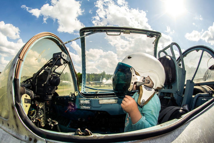 Side View Of Girl Sitting In Air Vehicle Against Cloudy Sky