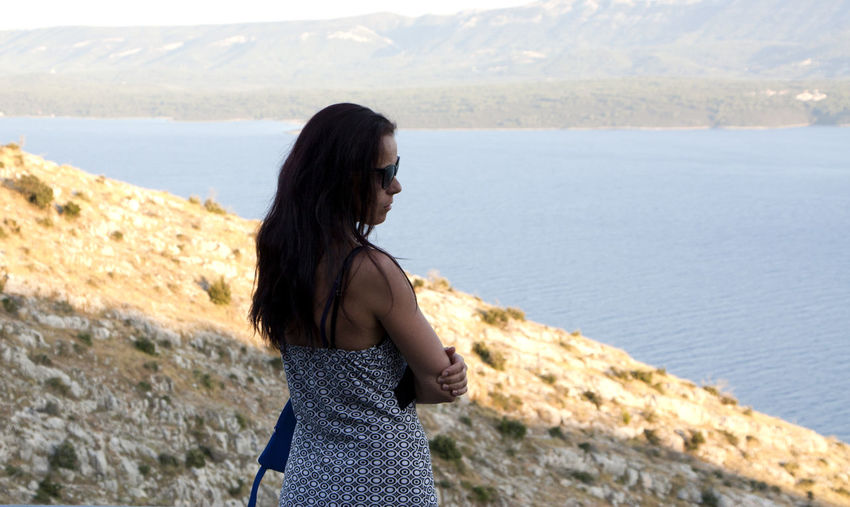Side view of young woman wearing sunglasses standing on hill