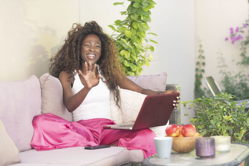 Mid Adult Woman Using Laptop While Sitting On Sofa At Home