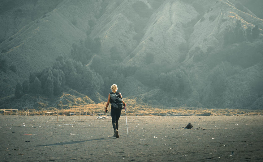 Full length of woman walking on land against mountains
