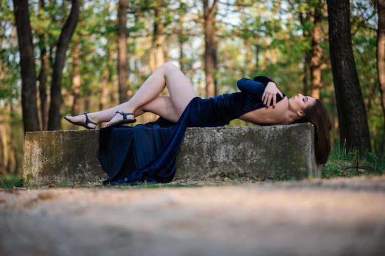 Side view of young woman lying down on land