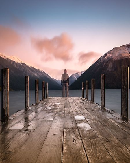 Rear view of woman standing on pier over lake against sky during sunset