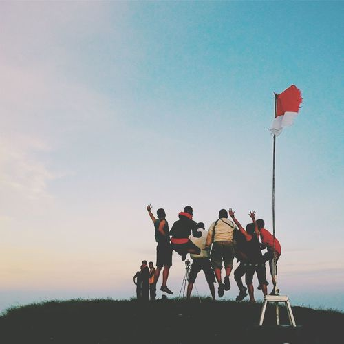 Low angle view of friends jumping on hill by indonesian flag at sunset