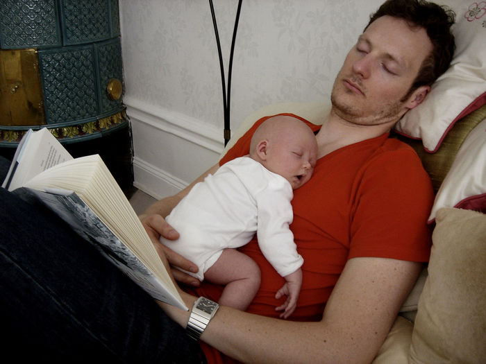 A father sleeping while reading with his baby daughter sleeping on his chest. Baby Babyhood Bonding Child Childhood Daughter Family Father Indoors  Love Parent Positive Emotion Relaxation Togetherness