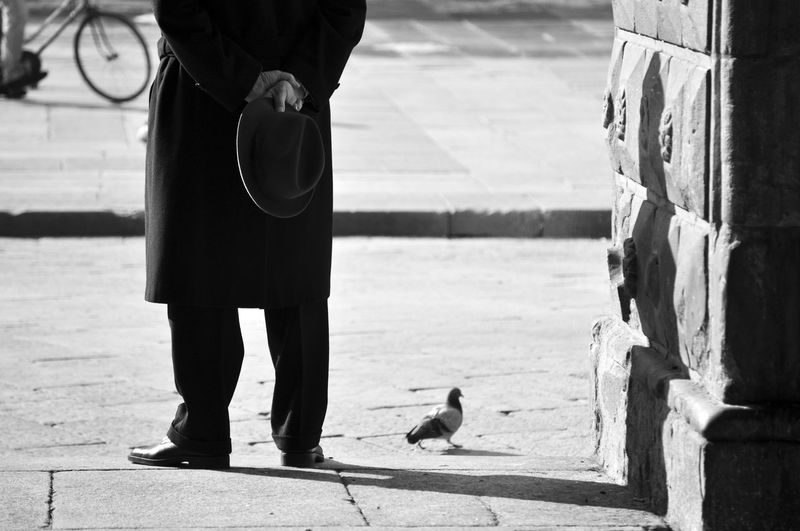 The man with the hat EyeEmNewHere Hat Biancoenero Bird Blackandwhite City Footpath Low Section Men One Animal Outdoors People Real People Rear View Street Streetphotography