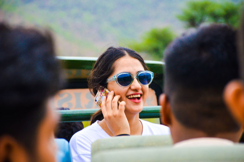 Smiling woman wearing sunglasses talking on smart phone
