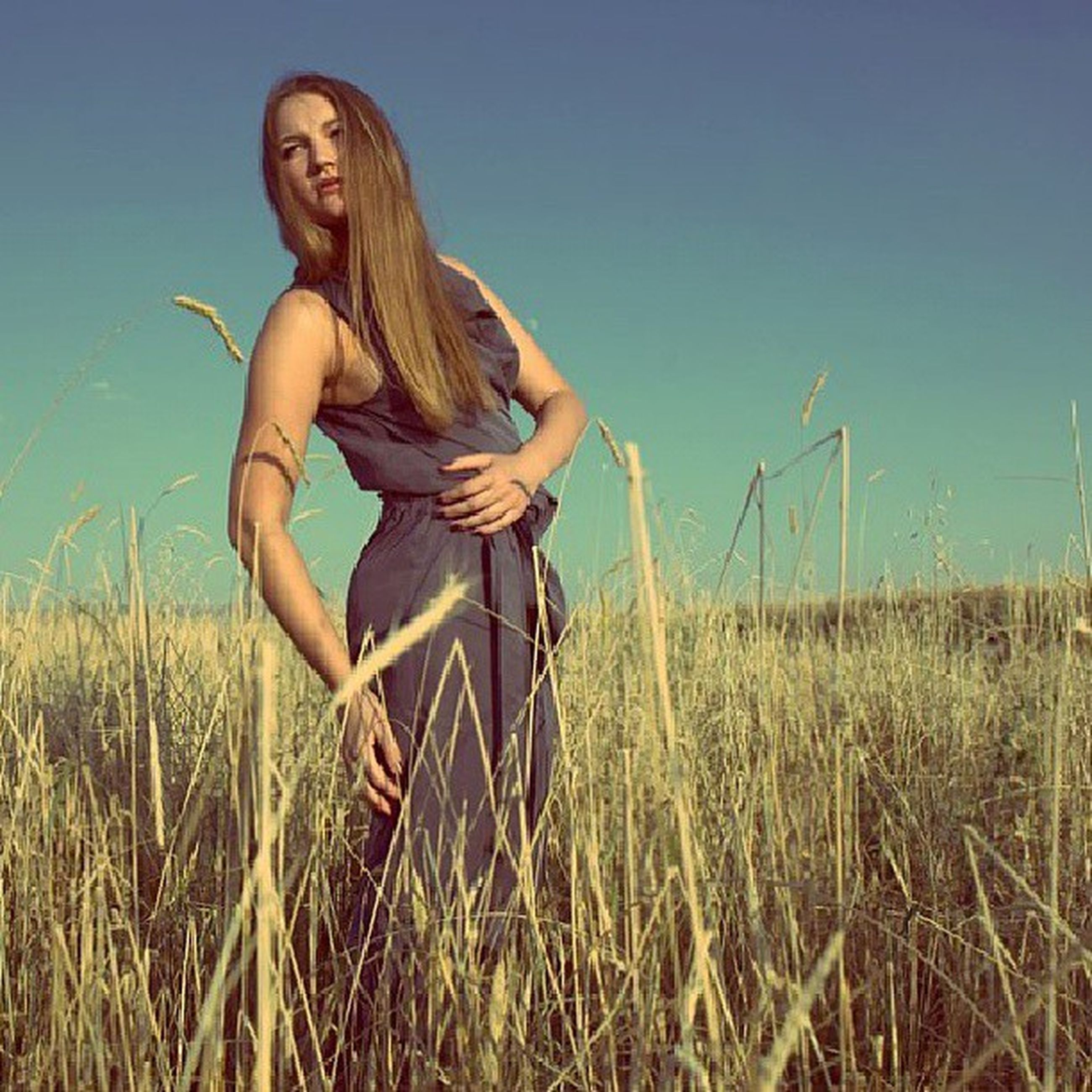 grass, lifestyles, leisure activity, young adult, person, casual clothing, full length, field, young women, three quarter length, standing, long hair, plant, grassy, clear sky, sky, nature, landscape