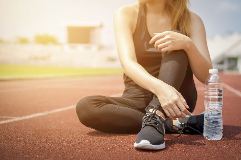 Fitness sport woman in black sportwear with drinking water bottle. Adult Day Exercising Focus On Foreground Front View Full Length Hairstyle Healthy Lifestyle Lifestyles One Person Outdoors Real People Running Track Shoe Sitting Sport Sports Clothing Track And Field Women Young Adult Young Women