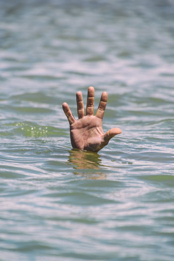 Cropped image of person drowning in sea