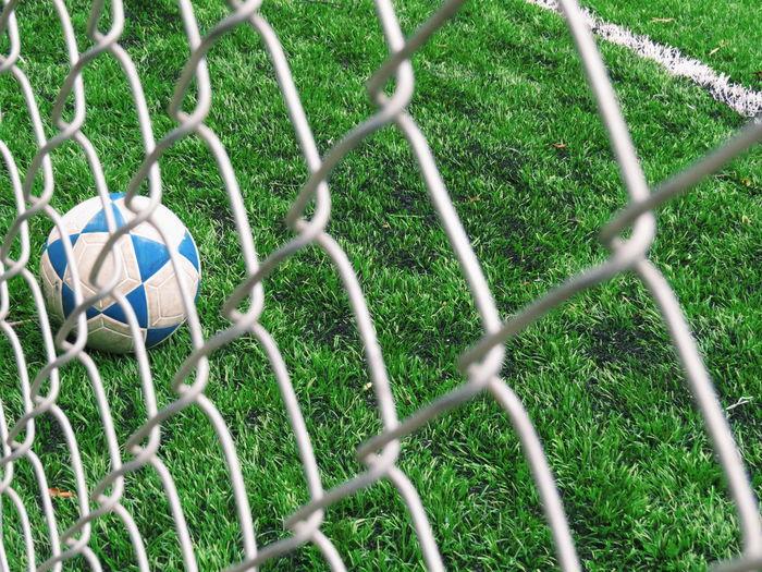 Soccer ball on field seen through chainlink fence