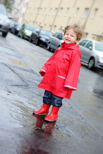 Full length of boy with umbrella on road