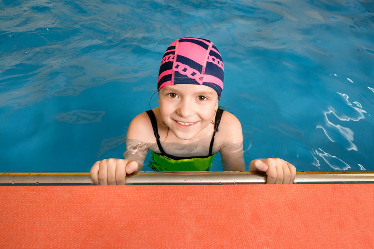 High angle portrait of smiling girl in swimming pool