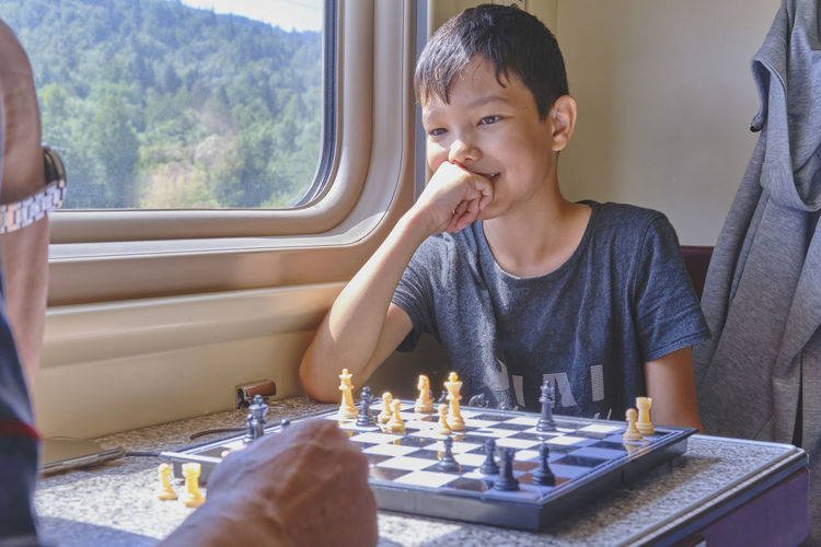 Asian boy smiling and playing chess in the train travel, table games concept