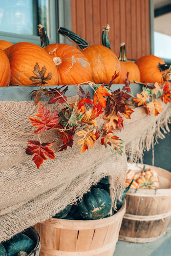Red, green pumpkins in baskets by store on farm. autumn fall harvest. fresh seasonal vegetables.