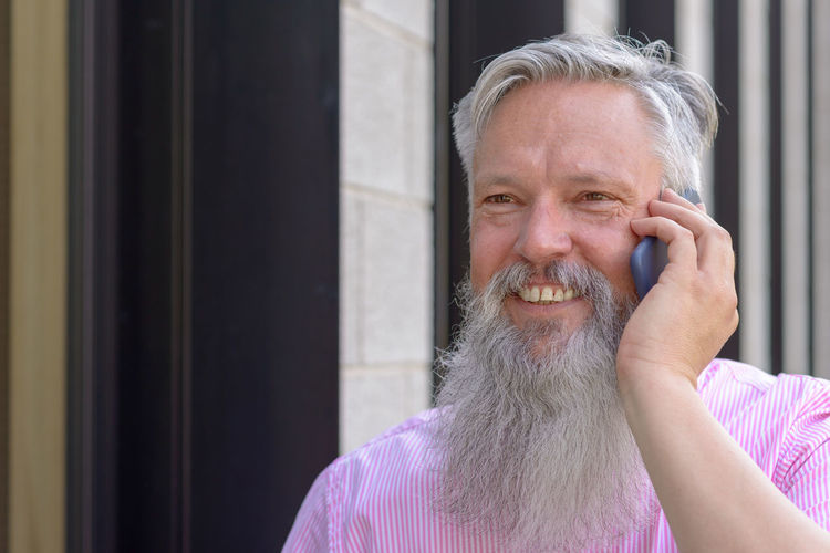 Mature Man With Beard Talking On Phone While Standing Outdoors