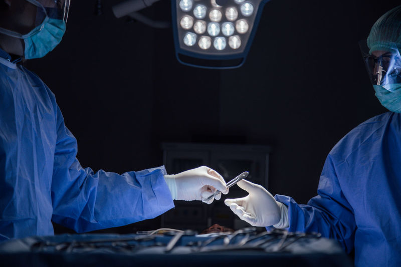Surgeons working in illuminated operating room