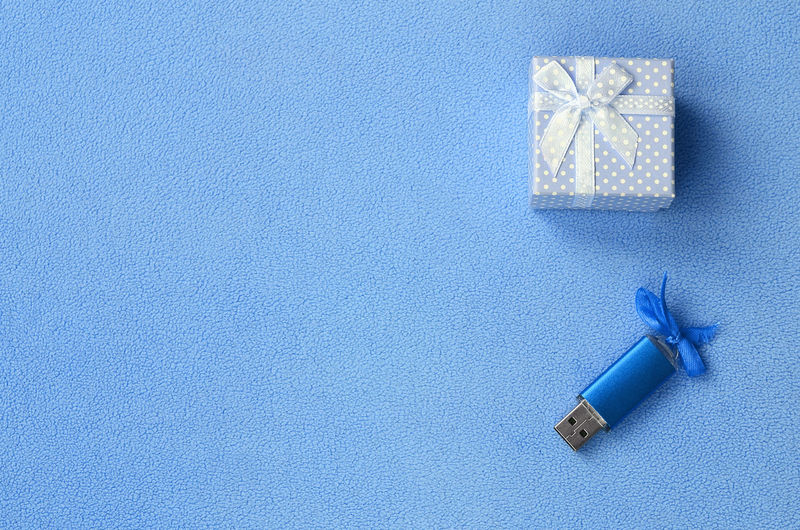 High angle view of usb stick and gift against blue background