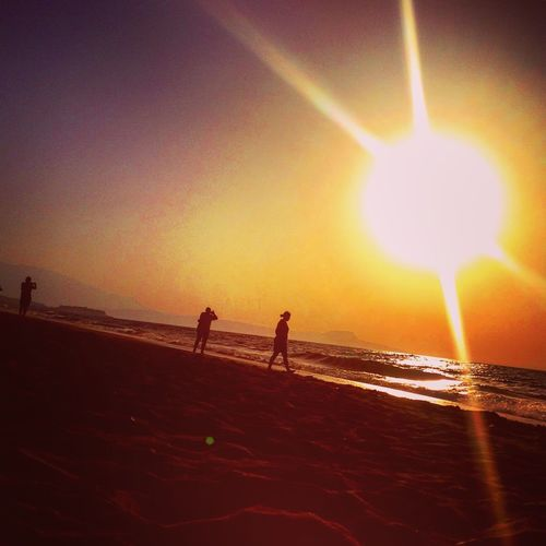 Beach Beauty In Nature Horizon Over Water Idyllic Leisure Activity Lens Flare Lifestyles Orange Color Outdoors Scenics Sea Shore Sun Sunbeam Sunlight Sunset Sunset At The Beach Sunset Silhouettes Tourism Tranquil Scene Tranquility Unrecognizable Person Vacations Water