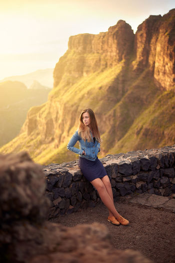 High angle view of woman standing by retaining wall against mountain