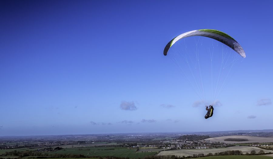 Paraglider flying in clear sky