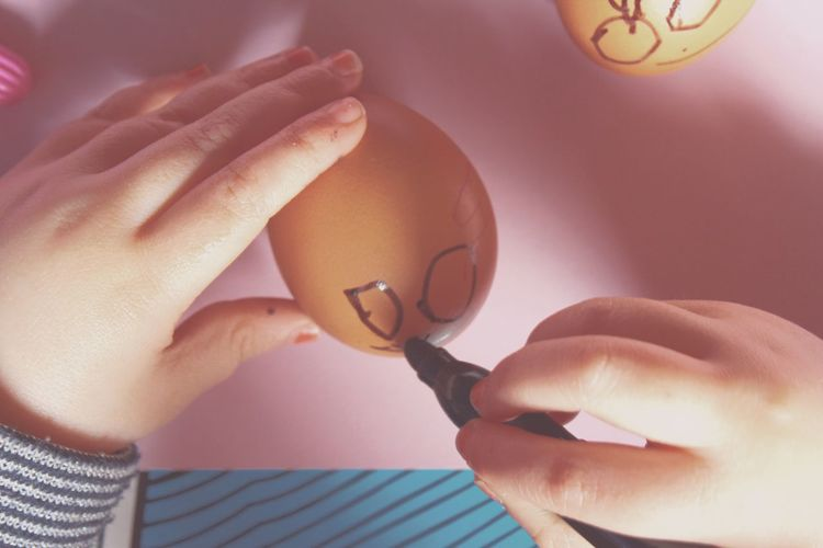 Cropped image of person drawing face on egg at home