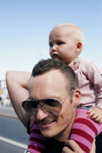 Close-Up Of Father Carrying Son On Shoulder Against Clear Sky