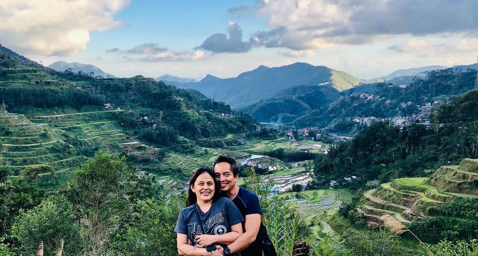Portrait of smiling couple standing mountains against sky
