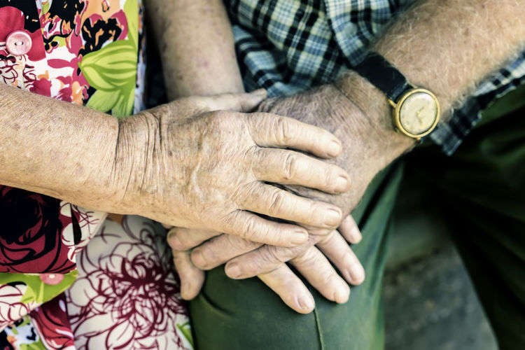 Midsection Of Senior Couple Holding Hands