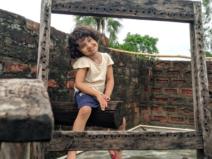 Portrait of smiling little girl sitting outdoors