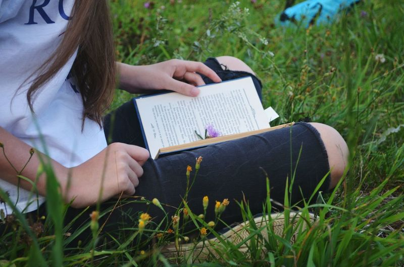 Cropped image of woman reading book while sitting at grassy field
