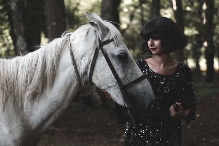 Young Woman Standing By Horse In Forest