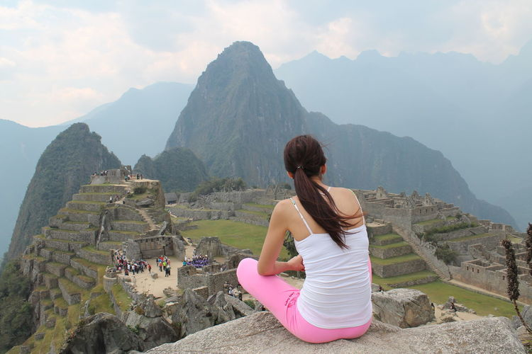 Young woman sitting on the rock and enjoying beautiful view of Machu Pichu in Peru Ancient Ancient Civilization Archaeology Beauty In Nature Beauty In Nature Casual Clothing History Lifestyles Nature Old Ruin One Person Outdoors Peru Real People Scenics Sitting On The Rock Travel Eyeemtravel  Young Women EyeEmNewHere EyeEmPremiumShot Premium Collection Eyeemtravel  Eyeemtraveler✌ Connected By Travel
