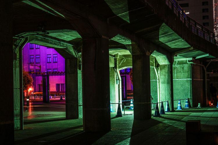 Illuminated street light on empty road amidst buildings at night