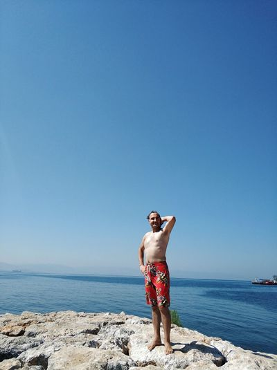 Full length of shirtless man standing on rock at beach against clear sky