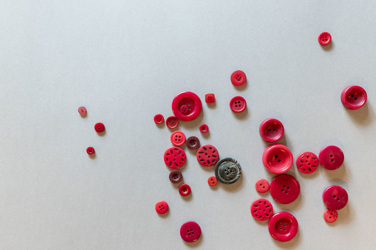 High angle view of red buttons on grey background Large Group Of Objects Studio Shot Indoors  Colored Background Backgrounds No People Button Multi Colored Choice Still Life Variation Close-up Shape High Angle View Arrangement Table Design Pattern Bead Circle Colors Group Of Objects Decoration Craft Textured  Creativity Geometric Shape Order One Of A Kind  Art is Everywhere