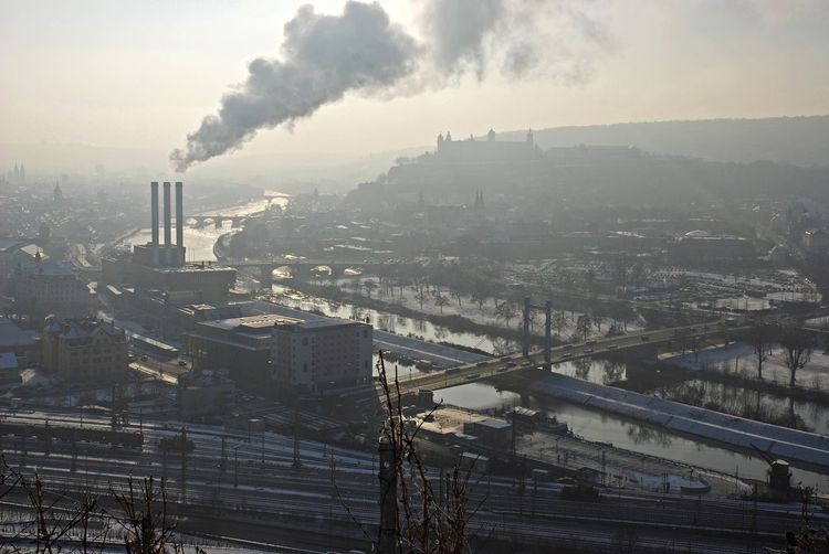 Factory Emitting Smoke By River In City