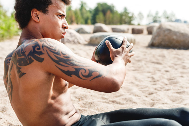Medicine Ball Sand Lifestyles Real People Tattoo Day Outdoors One Person Fitness Training Workout African American Abdominal Bare Chest Males  Exercising