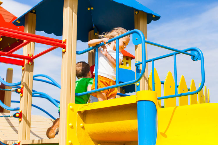 Low angle view of girl standing on slide in playground