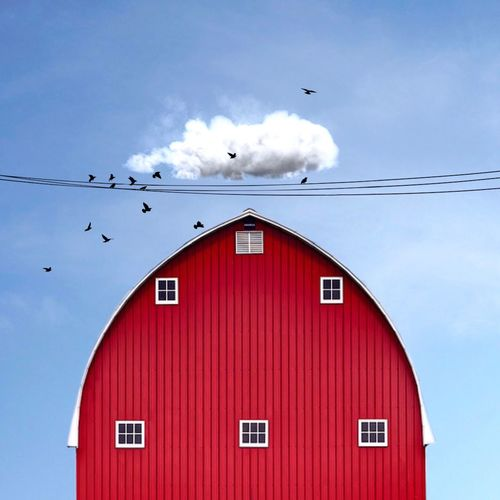 Low angle view of red barn against blue sky