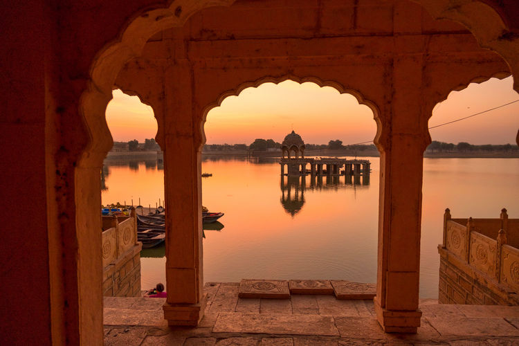 Sunrise over stone tower and historical building in Gadi Sagar lake, Jaisalmer, India. Ancient Civilization Arch Architectural Column Architecture Building Building Exterior Built Structure Gadisagar Temple Gadisarlake History Jaisalmer Nature No People Old Outdoors Reflection Sky Sunset The Past Tourism Travel Travel Destinations Water