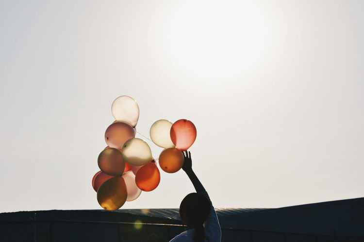 Rear view of woman holding balloons against clear sky on sunny day