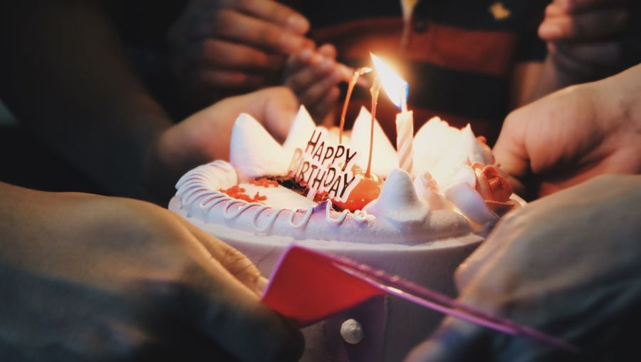 Close-up of hand holding birthday cake
