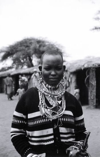 Portrait Of Woman Wearing Necklaces While Standing Against Huts