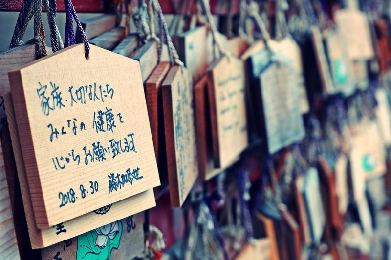 Close-up of traditional japanese wishing text planks hanging