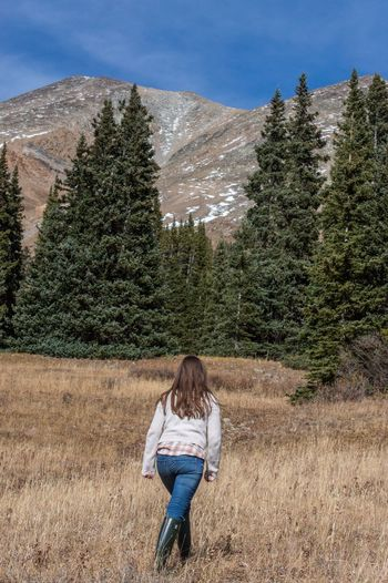 Rear view of woman walking on grassy field against mountains