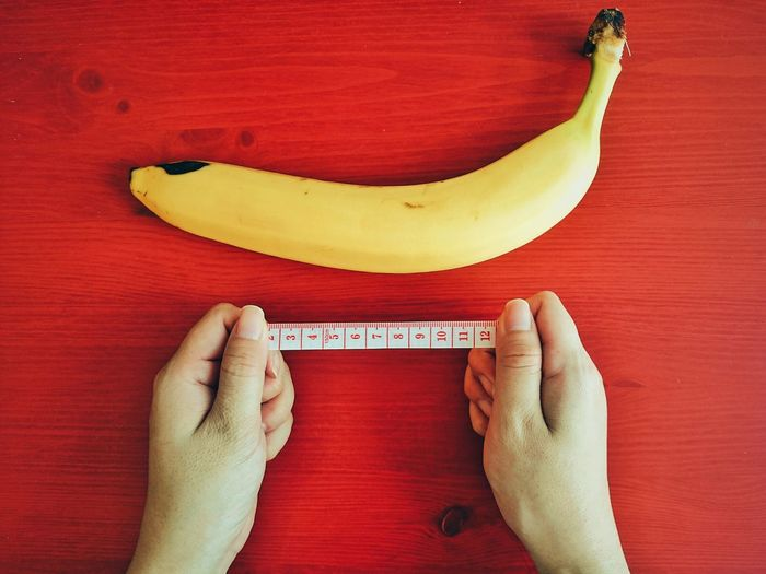 Cropped image of hand holding tape measure by banana on wooden table