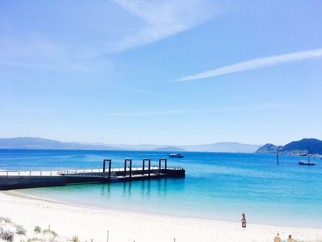 Beach Sea Sand Water Blue Sky Scenics Beauty In Nature Nature Day Tranquil Scene Outdoors Horizon Over Water Tranquility Summer Vacations Real People People In The Background Mountain Nautical Vessel