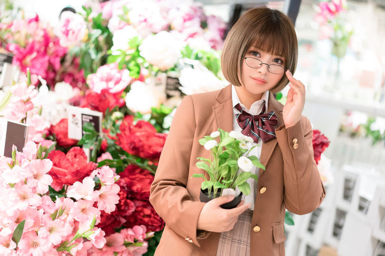 Portrait of woman holding plant standing at flower shop